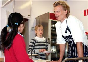 Kocken Paul Svensson i samtal med två elever på Bäckahagens skola i Bandhagen.  foto TV4